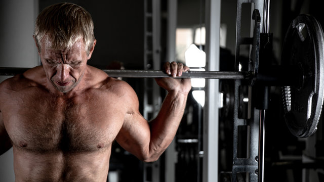 Muscular adult brutal man doing barbell squats in the gym. Portrait of caucasian authentic bodybuilder doing workout exercises