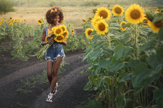 Happy young black woman walks in the sunflower field. Smiling dark-skinned girl with with a bouquet of sunflowers and curly hair.