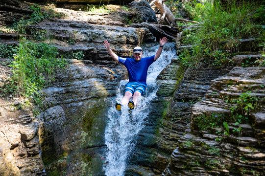 Caucasian male on rock waterslide into Devils bathtub in Spearfish Canyon of the Black Hills South Dakota