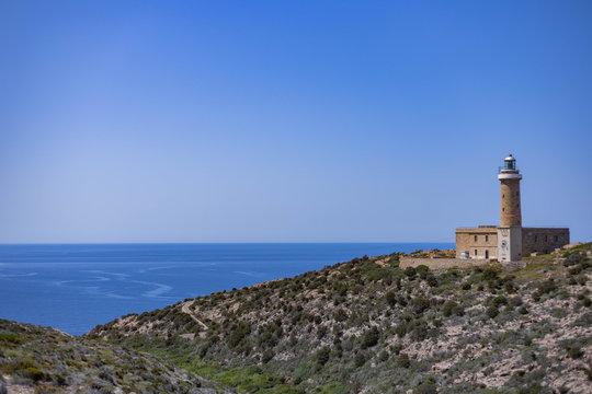 View of Mediterranean Sea with lighthouse from Belvedere di Capo Sandalo, Carloforte, Sardinia, Italy