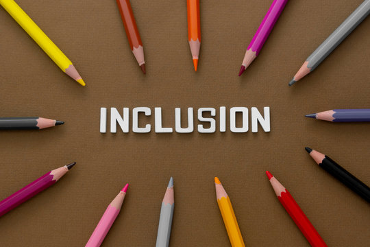 Inclusion word with colorful pencils over brown background. Equality, community integration concept. Top view.