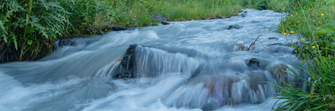 Water in mountain river from glacier on valley. Beautiful landscape wide banner. Long exposure shot