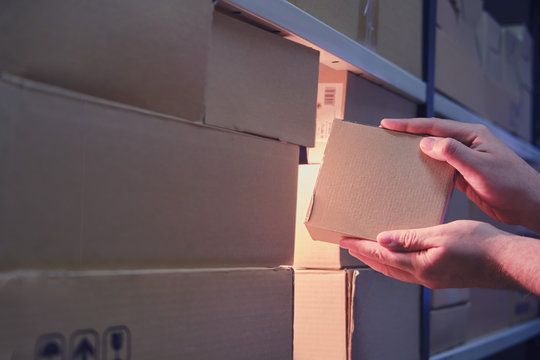 Male hands in a warehouse with box, night theft