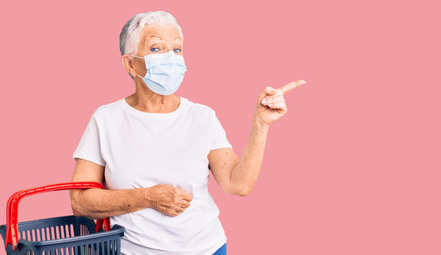Senior beautiful woman with blue eyes and grey hair wearing shopping basket and medical mask smiling happy pointing with hand and finger to the side