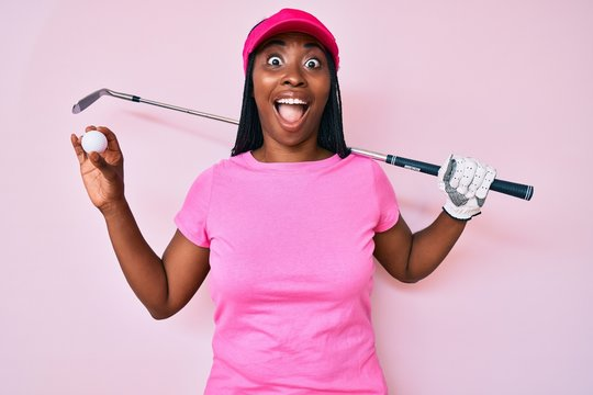 African american golfer woman with braids holding golf ball celebrating crazy and amazed for success with open eyes screaming excited.