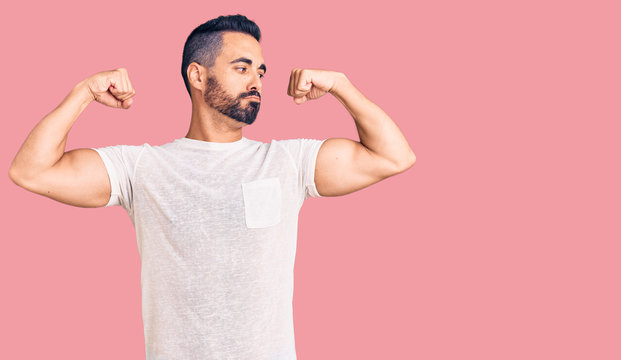 Young hispanic man wearing casual clothes showing arms muscles smiling proud. fitness concept.