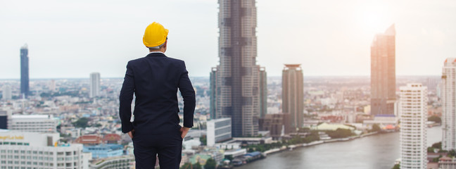 architect man wear black suit and yellow helmet view from back standing on building looking for cityscape. looking for future concept. Fotomurales