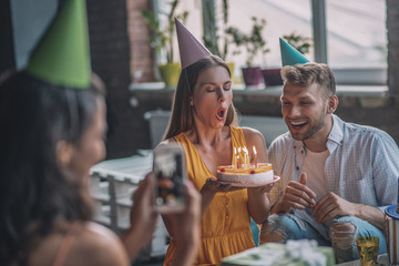 Woman taking picture of her friend blowing out candles