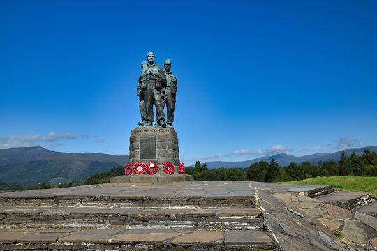 Public Commando Memorial near Spean Bridge, Scottish Highlands. Poppy wreaths at commandos feet. Summer with bright blue sky. Hills in background.
