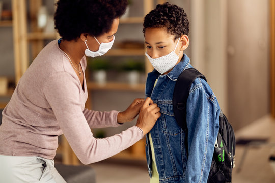 Black boy with face mask preparing to go back to school during coronavirus pandemic.