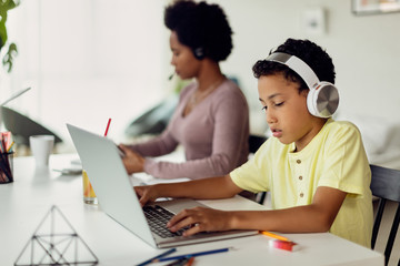 African American boy using laptop while his mother is working in the background.