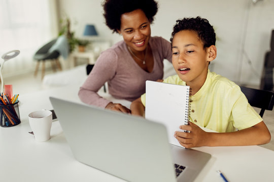 Black boy making video call over laptop while homeschooling with his mother.