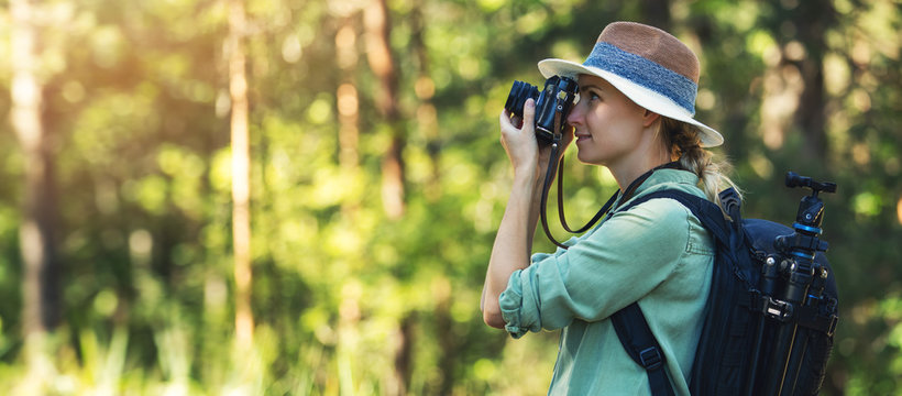 nature photography - woman photographer taking picture with analog film camera in forest. banner copy space