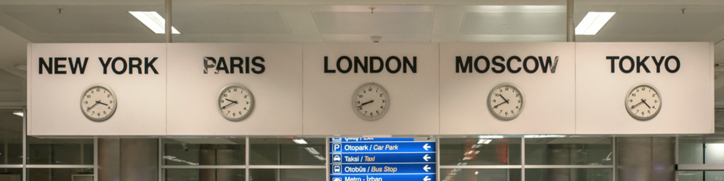 five white international clock with different time zone hanging on banner in airport station