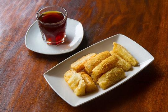 Deep fried cassava root with a cup of coffee. Brazilian Mandioca Frita (deep fried cassava/ manioc/yuca). Feijoada side dish