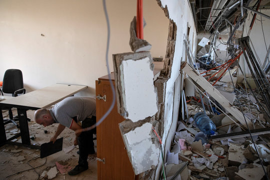 An employee cleans an office area inside Lebanon's Electricity Company (EDL) headquarters, in the aftermath of a massive explosion at the port area, in Beirut