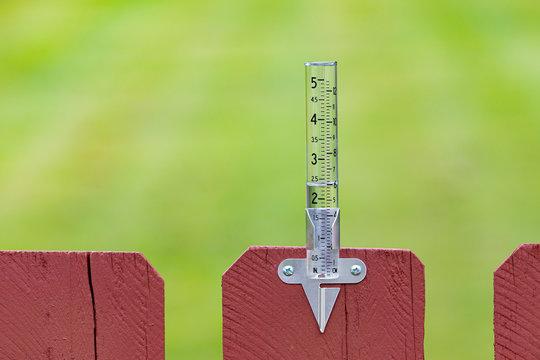 Closeup of rain gauge with rainwater, Concept of weather, rain, drought, flooding and precipitation.