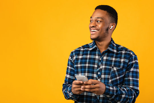 Happy African Guy With Smartphone Listening To Podcast, Studio Shot