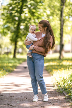 A young mother walks with a one-year-old baby, holds him in her arms, hugs. Communication with the child for his harmonious development