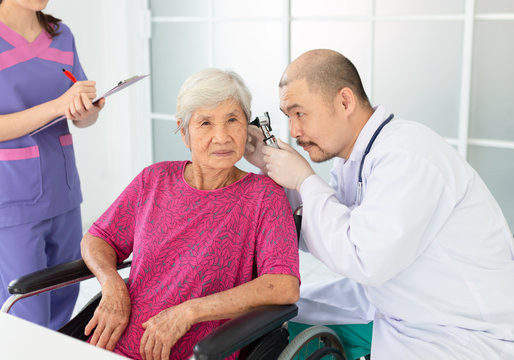 asian man use otoscope looking in ear canal of old patient, Otorhinolaryngology disease, elderly health check up
