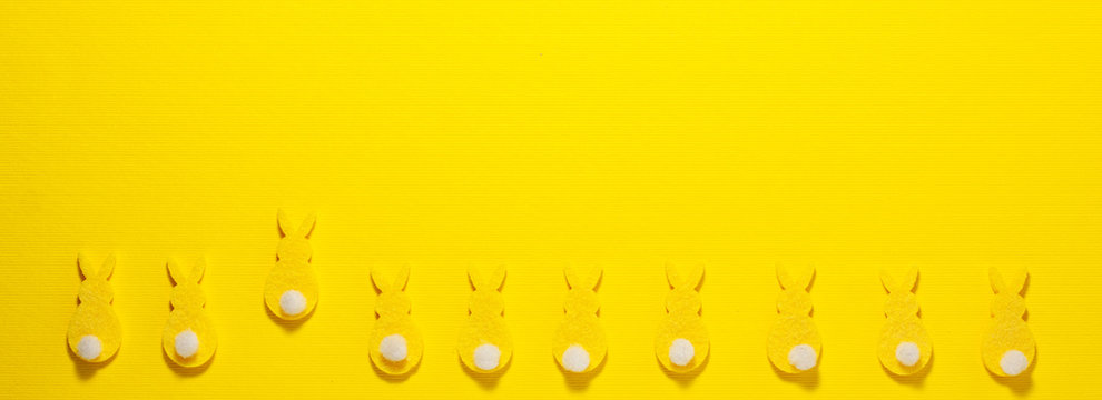 Yellow velvet bunnies on yellow background at the battom with space for text. Flat lay top view. Easter concept.