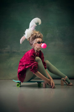 Blowing bubble with gum on skateboard. Young woman as Marie Antoinette on dark green background. Retro style, comparison of eras concept. Beautiful model like classic historical character, old