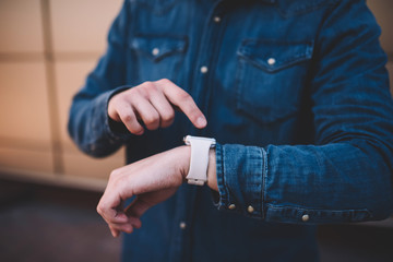 Cropped image on man checking notification on digital smartwatch display planning day with modern organizing app, man's hands with wearable computer wrist watch sending new updates and messages