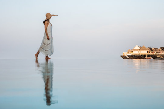 Side view of young woman walking on edge of infinity pool against sky