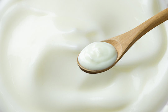 yogurt on spoon wooden  on yogurt background