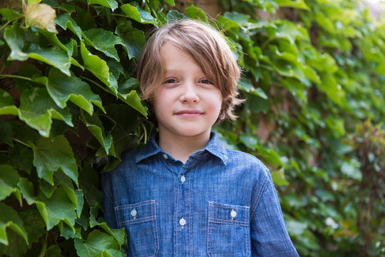 portrait of 7 year old boy standing in front of green ivy wall