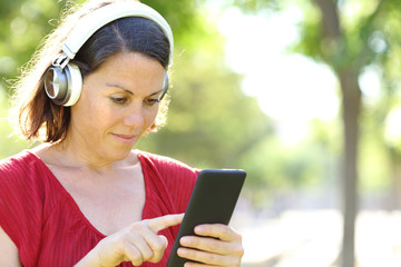 Adult woman with headphones listens to music on phone