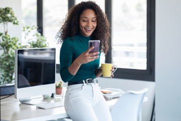 Smiling young business woman sending messages with mobile phone sitting on the desk in the office.