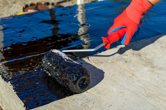 Waterproofing coating. Workers hand in protective gloves applies bitumen mastic on the foundation. Roofer cover the rooftop polymer modified bitumen waterproofing primer, with a roller brush