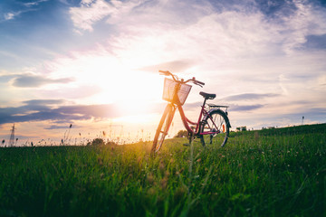 Female bicycle with a basket stands on a green field at sunset, summer vacation adventure