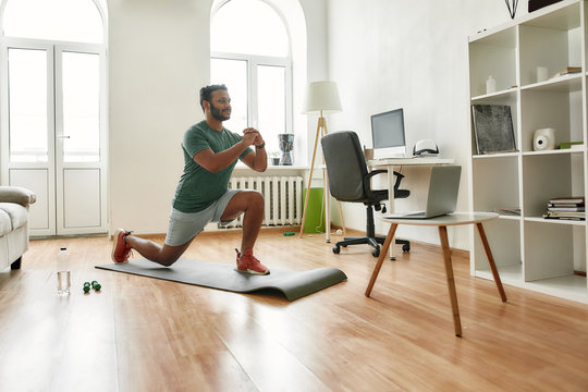 Fitness matters. Young active man showing exercises while streaming, broadcasting video lesson on training at home using laptop. Sport, online gym concept