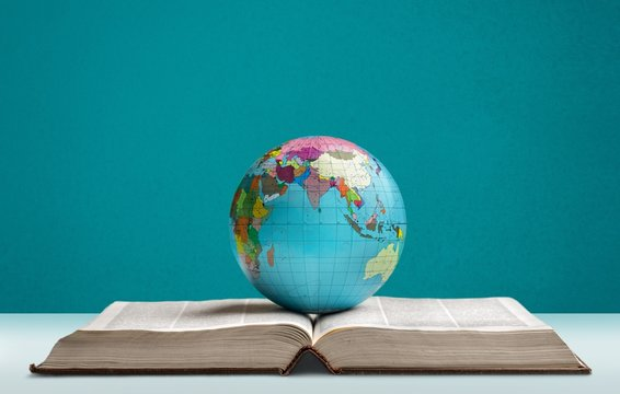 Heavy book and globe of a planet on the desk