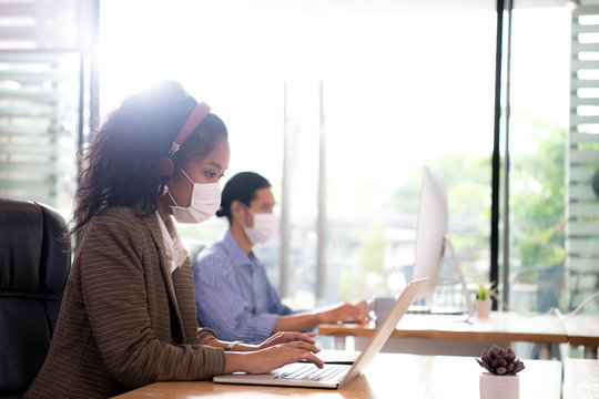 Asian female office worker wearing face mask working in new normal office and doing social distancing during corona virus covid-19 pandemic