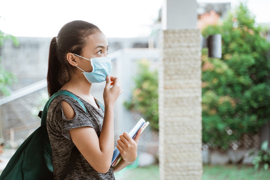 A portrait of a teenage student wears and holds a mask standing outside the house. Back to school concept after pandemic
