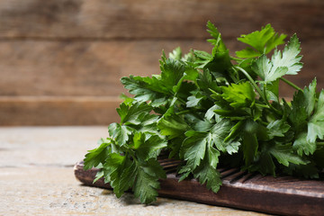 Board with fresh green parsley on wooden table, closeup