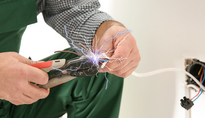 Electrician receiving electric shock while working, closeup