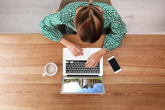 Woman choosing new house online using laptop or real estate agent working at table, top view
