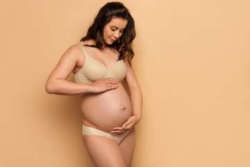 pregnant woman in underwear touching belly on beige