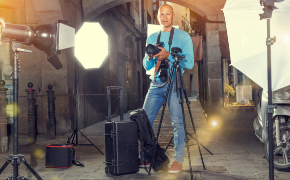 Portrait of male photographer standing with camera among professional photo equipment at old city street