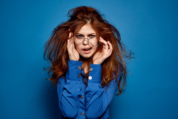 Energetic red-haired woman in blue shirt with glasses gesturing with hands
