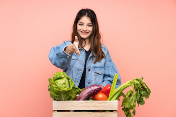 Young farmer woman holding a basket full of fresh vegetables handshaking after good deal
