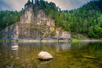 An epic landscape of Ural nature on the Chusovaya river with large rocks along the river.