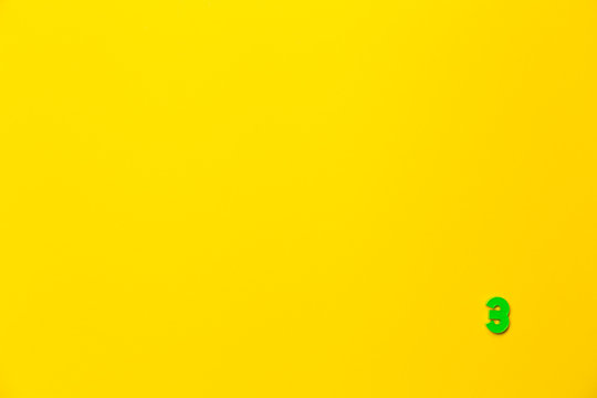 Number 3, three, the third of the plastic baby green toy number is located in the lower right corner on a yellow paper background. Banner on the topic of page numbering, timing or day in the calendar