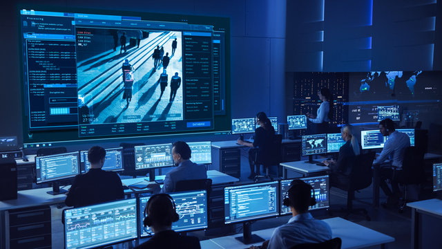 Team of Professional Cyber Security Data Science Engineers Work on Surveillance Tracking Shot of People Walking on City Streets. Big Dark Control and Monitoring Room with Computer Displays.
