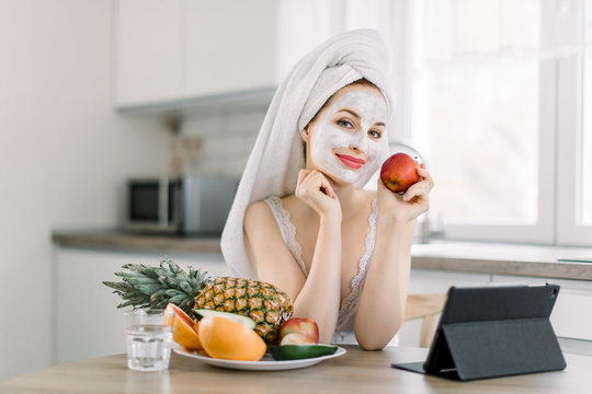 Woman with mud treatment facial mask enjoying spa procedures at home, sitting at the table in the kitchen, eating red apple and using her ebook or tablet. Skin care and healthy lifestyle concept