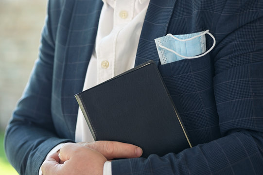 Man Hold Holy Bible with a medical mask
